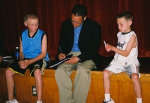 Mike Reiss of the Boston Globe (center in black jacket) signs an autograph for reporters from the Cunniff Kids News after his press conference June 11, 2008.