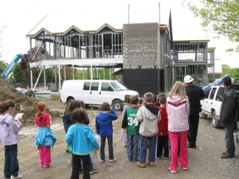 Police Officer Lloyd Burke (second from right, with hard hat) surveys the progress at his future workplace, the Watertown police station, in May 2009.
