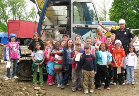 Reporters from the Cunniff Kids News and Officer Lloyd Burke (second from right, with hard hat) pose near one of the many machines at the site of the new Watertown police station in May 2009. At the time, the station was scheduled to open in Spring 2010.
