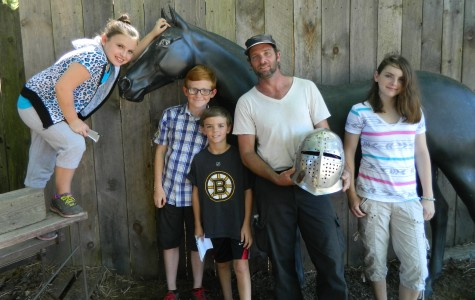 Stuntman Joe Darrigo (in white shirt) poses with reporters from the Cunniff Kids News on the grounds of King Richard's Faire on Aug. 26, 2014, during his preparation for the opening of the Renaissance fair's 33d season in Carver, Mass.