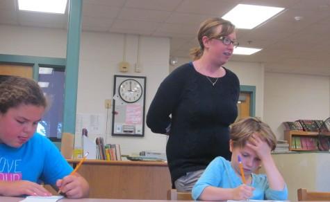 New Cunniff art teacher Jaclyn Meyer walks behind Cunniff Kids News reporters during an interview in the newsroom Oct. 6, 2015.