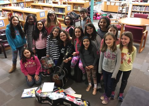 Singer Allie Moss (with guitar) poses with Cunniff Kids News reporters after an interview in their newsroom at Cunniff Elementary School in Watertown, Mass., on March 21, 2017.