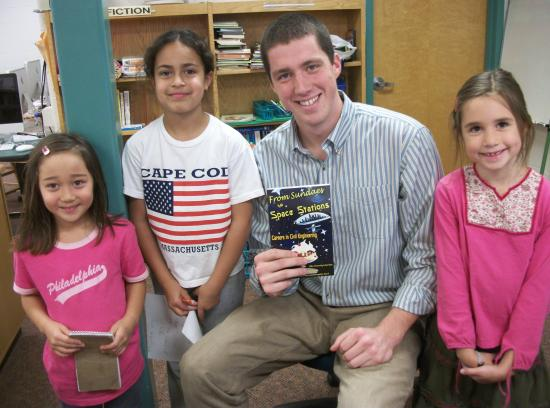 John Quinn (seated) takes a moment from checking in a new library book to pose with reporters from the Cunniff Kids News