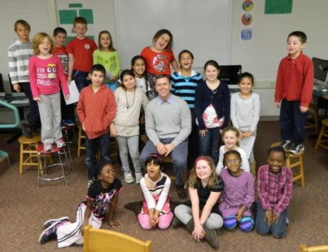 New fifth-grade teacher Lucas Donohue (seated in center) poses with the Cunniff Kids News staff after his interview in the newsroom.