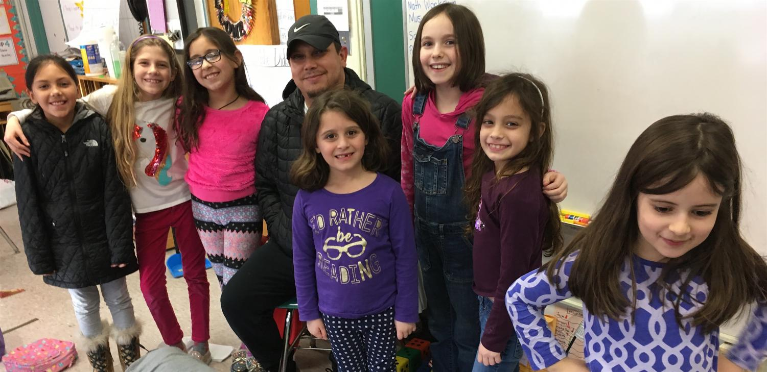 Milton Contreras (center, wearing hat) poses with reporters from the Cunniff Kids News after a visit to the newsroom Wednesday, Jan. 30, 2019.