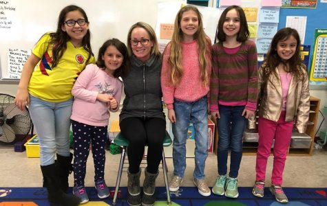 Watertown School Committee member Amy Donohue (third from left) poses with some student reporters from the Cunniff Kids News after an interview about the 2019 Watertown Spelling Bee.